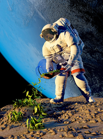 Astronaut planting grass on the planet. Imagens