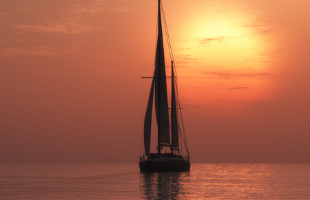 Yacht in the sea at sunset Stock Photo