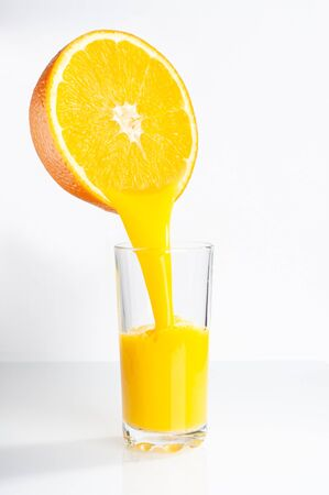 Fresh orange juice is poured from half an orange into a transparent glass. place for inscription. Reklamní fotografie