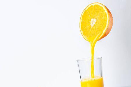 Fresh orange juice is poured from half an orange into a transparent glass. place for inscription. Banco de Imagens