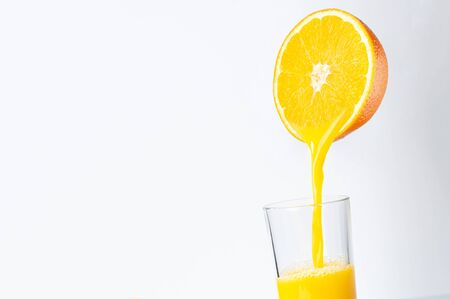 Fresh orange juice is poured from half an orange into a transparent glass. place for inscription. 스톡 콘텐츠