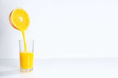 Fresh orange juice is poured from half an orange into a transparent glass. place for inscription. 스톡 콘텐츠 - 139726626