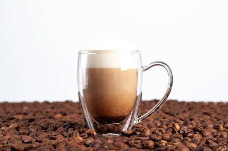 A transparent double-bottom latte cup stands among coffee beans on a white background. Copyspace.