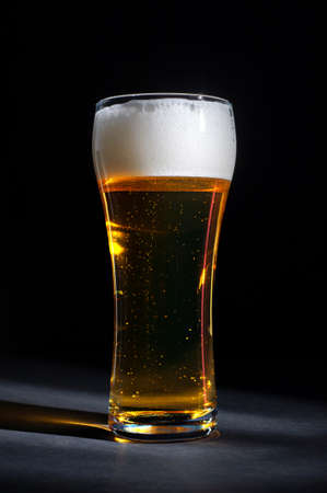 fresh beer in a beautiful tall glass on a black background. High quality photo