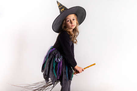 little girl in halloween costume holding a pumpkin in her hands on a white background. High quality photo