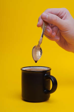 girls hand stirring a spoon of coffee on a yellow background. High quality photo