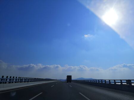 On the highway, the vehicles seem to be driving into the clouds, blue sky and white clouds, hoping for hope Stok Fotoğraf