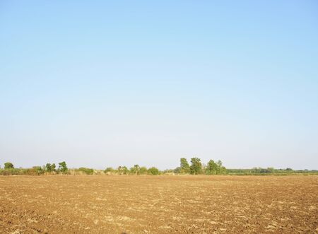 Plowed land for sowing in the corn field. Landscape in the countryside with fields against the sky.