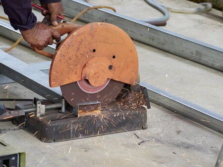 Worker cut steel with cutting machine circular disc cuts off part of iron until sparks occur while cutting steel. 版權商用圖片