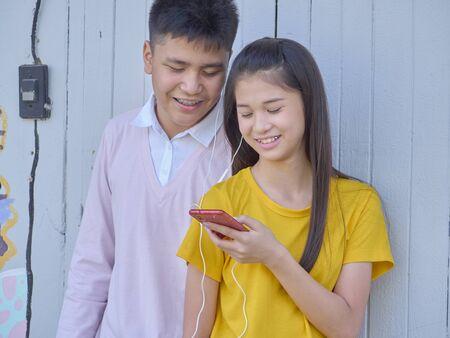 Les jeunes adolescents, hommes et femmes, utilisent leurs smartphones en plein air dans le parc.