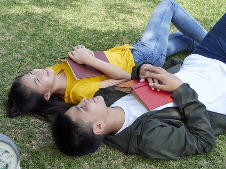 Two students were smiling cheerful and reading the book on grass in the park.