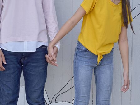 Close up of young couple holding hands on gray old wood wall background 写真素材 - 143213026