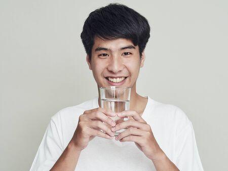 Portrait de jeune homme asiatique souriant tenant un verre d'eau. Isolé sur fond blanc. Banque d'images