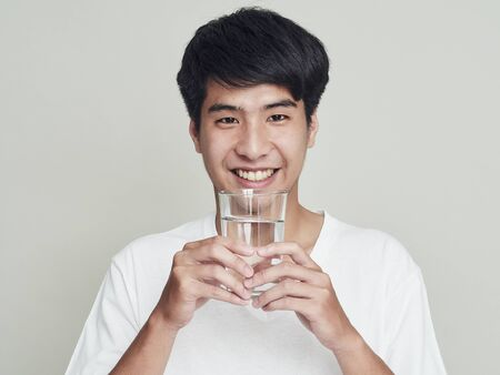Portrait of smiling young asian man holding water glass. Isolated on white background.