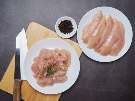 Raw chicken tenderloin and rosemary, wooden board, knife, pepper, salt over stone kitchen cooking table. space for text, top view