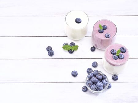 Glass of yogurt blueberry and mint leaves placed on white wooden table. Healthy breakfast, diet food. space for text Reklamní fotografie