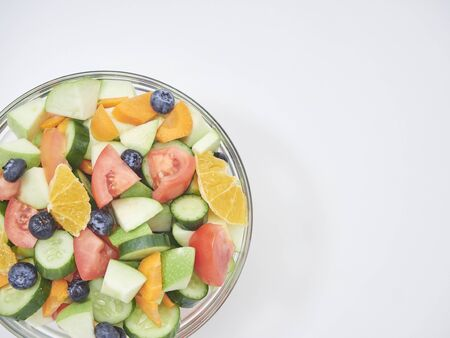 Mixed vegetable salad with fresh fruit in a glass bowl on a white background. carrot, orange, blueberry, Apple, lemon, tomato, cucumber. Healthy menu design. diet food. Top view, copy space, flat lay.