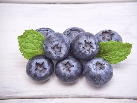 Blueberry and fresh mint leaves on white wooden table. Berries watercolor image for healthy menu design. Close up