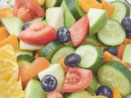 Mixed vegetable salad with fresh fruit in a glass bowl on a white background. carrot, orange, blueberry, Apple, lemon, tomato, cucumber. Healthy menu design. diet food. flat lay, close up