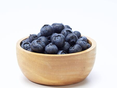blueberry in wooden bowl and wooden spoon on white background. Healthy food design. space for text 写真素材