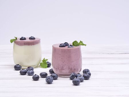 Two glasses of blueberry yogurt on a white wooden table. Healthy breakfast, diet food. space for text