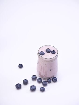 Healthy fresh blueberry yogurt isolated on a white background. Fruit vitamins for health. space for text