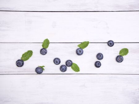 Blueberry and fresh mint leaves on white wooden table. Berries watercolor image for healthy menu design.