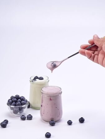 Woman hands holding a spoon and has a blueberry yogurt glass on a white background. Healthy breakfast, diet food