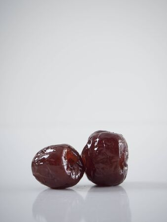 Boiled jujube with syrup on white background. Dried fruit. Space for text Фото со стока