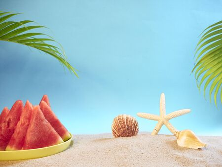 Summer holiday background with palm leaves,watermelon and sands on light blue copy space. Summer sea travel concept.
