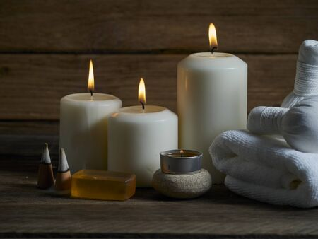 Spa composition with natural handmade soap, herbal compress ball on wooden background. Space for text