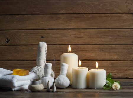 Spa set with alight candles and the smoke of burning frankincense on wooden table in the dark. Stock Photo