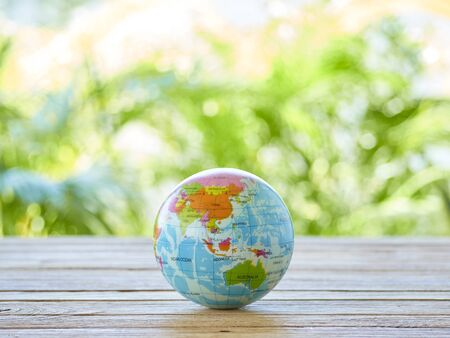 Globe on wooden table outdoor with blurred green tree garden nature in spring and summer.