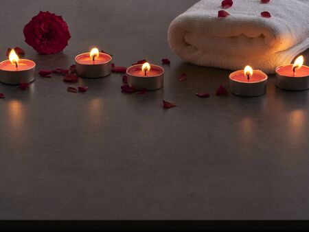 Beautiful spa composition of alight candles with rose on gray marble background.
