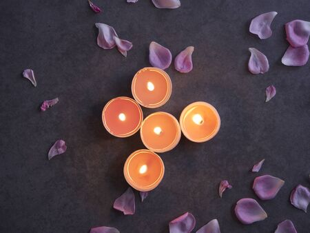 Beautiful spa composition of pink rose petals and alight candles on gray marble background in the dark.