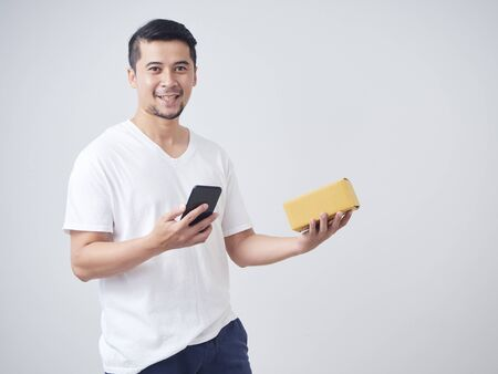 Young man uses smartphone to place an order and hold parcel box that has been deliver from an online shopping store.