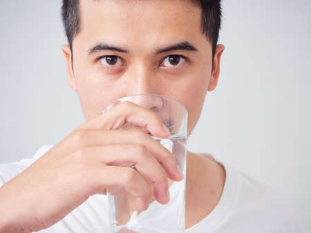 Close-up of young man in white t-shirt drinking water from a glass Reklamní fotografie