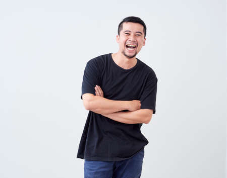 Portrait of young man laugh happily while standing in studio setting