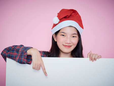 Cute teenage gir in santa hat pointing finger on blank poster while standing on pink background.