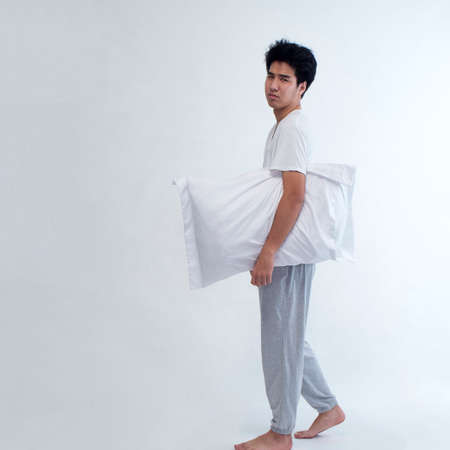Young man in pajamas embracing white pillow on white background