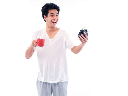 Young men in pajamas holding cup of coffee and alarm clock on white background