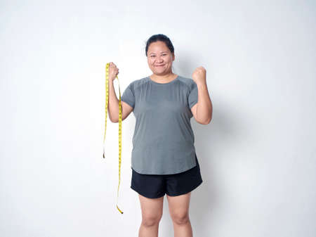 Fat woman with measuring tape on white background. Weight loss concept