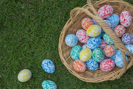 birdseye: Many colored Easter eggs in a Wicker basket, On the grass, Birdseye shot Stock Photo