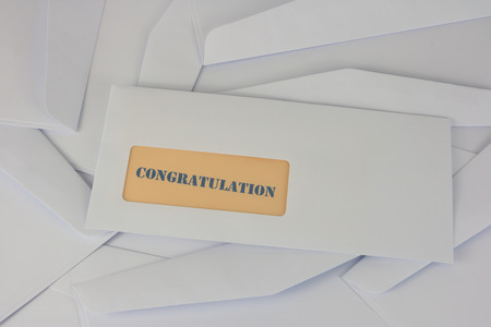 inform information: congratulation announcement from white envelope on heap of envelopes Stock Photo