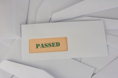 inform information: passed announcement from white envelope on heap of envelopes