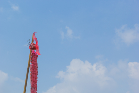 Red Firecrackers hang on pole with blue sky