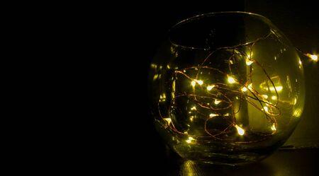 garland lanterns light bulbs in a glass bowl Imagens