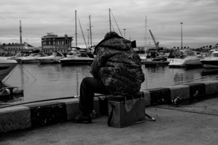 fishermen sitting with fishing rods on the background of yachts in black and white