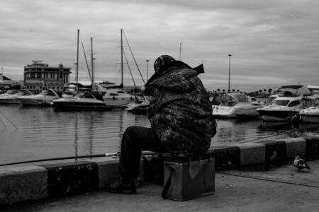 fishermen sitting with fishing rods on the background of yachts in black and white Archivio Fotografico