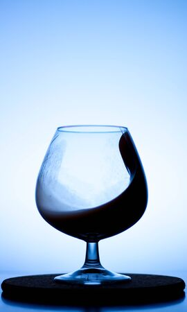 a splash of liquid in a glass wine glass. water pouring inside a glass wine glass. a curl of water in a wine glass. drink in a glass wine glass .splash in the glass